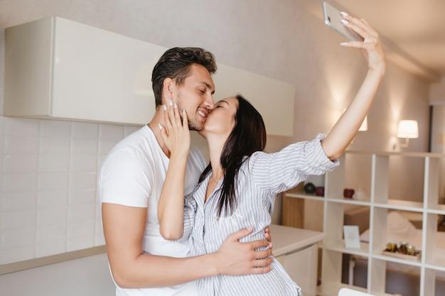 Engraçada senhora de cabelo preto em uma elegante camisa masculina fazendo selfie e beijando o namorado