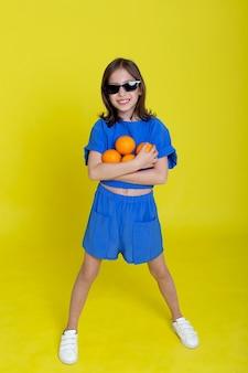 Engraçadinha brincalhão menina bonitinha alegremente segurando laranjas, na parede.