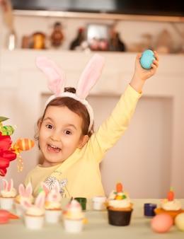 Engraçadinha criança usando orelhas de coelho e pintando ovo de páscoa na primavera em casa.