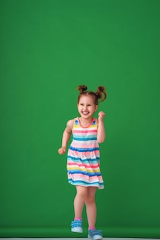 Engraçadinha de quatro anos em um vestido colorido e listrado corre e ri.
