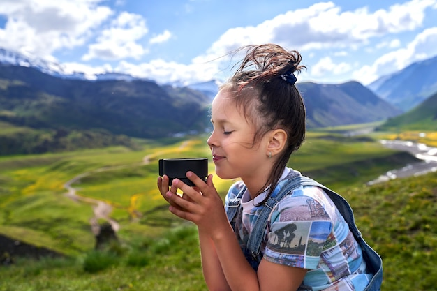 Engraçadinha linda garota segura uma caneca e bebe chá nas montanhas.