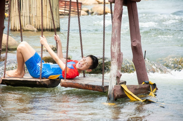 Engraçadinho gosta de jogar balançando no canal na zona rural da tailândia