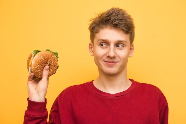 Engraçadinho segura um hambúrguer na mão e olha para ele