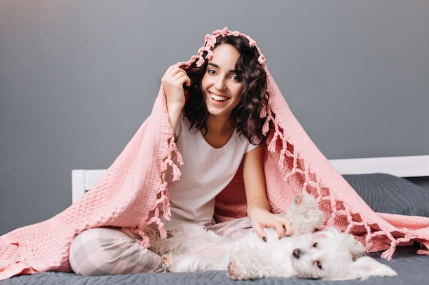 Engraçado adorável casa momentos de mulher jovem feliz de pijama sob o cobertor rosa, brincando com o cachorrinho branco na cama em apartamento moderno. sorridente, alegre, expressando positividade.