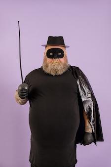 Engraçado adulto barbudo do sexo masculino com excesso de peso vestindo terno zorro com capa, máscara e espada de brinquedo em um fundo roxo no estúdio