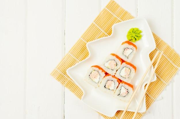 Engraçado árvore de natal comestível feita de sushi, ideia criativa para restaurante japonês na mesa branca. . feriado, celebração, conceito de arte de comida. copyspace.