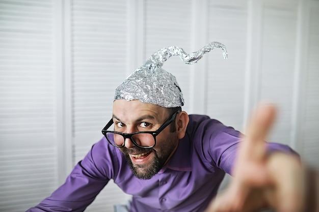 Engraçado barbudo em um boné de papel alumínio. fobias de arte conceitual. teoria da conspiração. conspiração. insanidade.