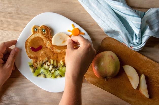 Engraçado café da manhã infantil: panquecas com frutas, parecendo uma tartaruga