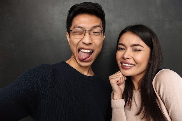 Engraçado casal asiático feliz posando juntos e fazendo selfie