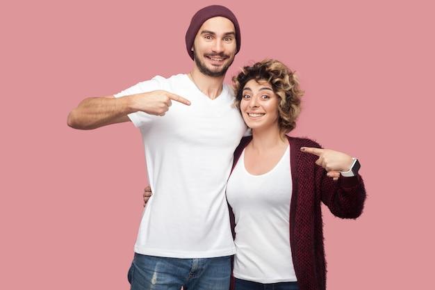 Engraçado casal de amigos no estilo casual, em pé, abraçando e apontando os dedos um para o outro, olhando para a câmera com felicidade e sorriso. isolado, interno, foto de estúdio, fundo rosa