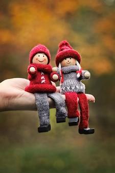Engraçado casal romântico de bonecos de madeira em malha está sentado na palma da mão