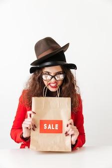 Engraçado caucasiana jovem segurando sacola de compras