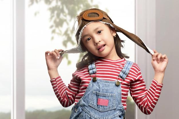 Engraçado criança asiática com chapéu de aviador e óculos jogando