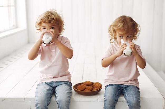 Engraçado crianças comendo biscoitos e bebendo leite