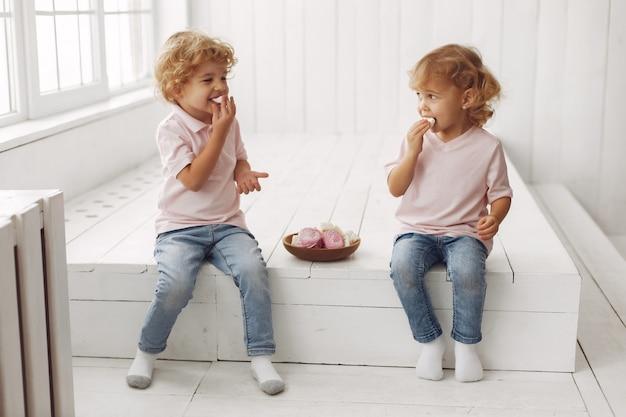 Engraçado crianças comendo biscoitos em casa