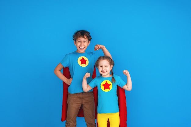 Engraçado crianças super herói poder em capas de chuva vermelhas e máscara.