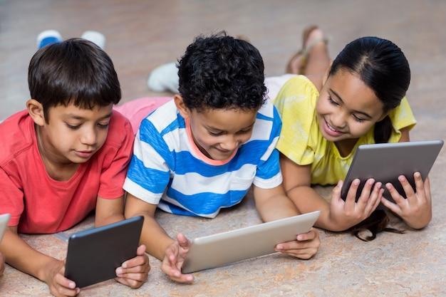 Engraçado crianças usando tablets digitais