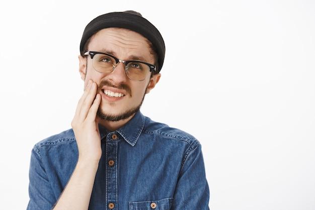 Engraçado descontente barbudo sentindo desconforto fazendo uma careta olhando para cima e franzindo a testa por causa de uma dor de dente dolorida segurando a mão na bochecha e reclamando de dor