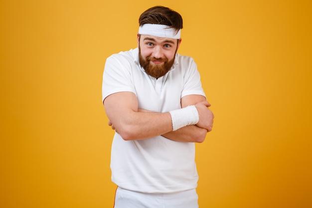 Engraçado desportista barbudo com braços cruzados