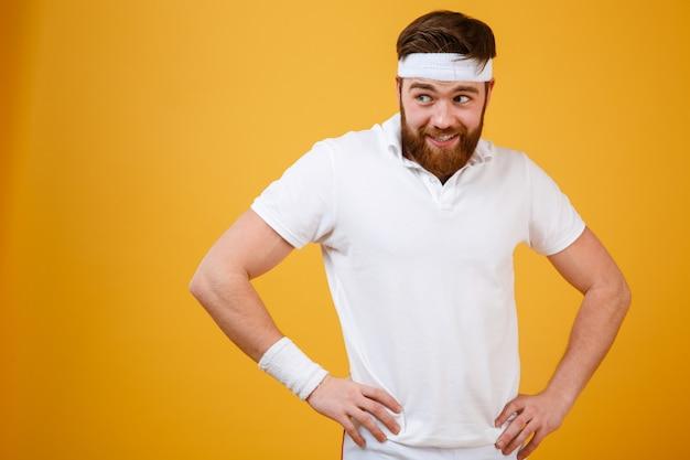 Engraçado desportista barbudo segurando os braços no quadril