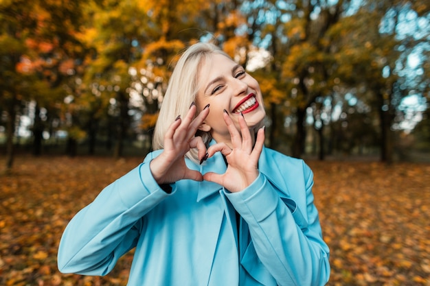 Engraçado e linda garota com um sorriso em um casaco azul mostra um sinal de amor em um parque de outono com folhagem amarela
