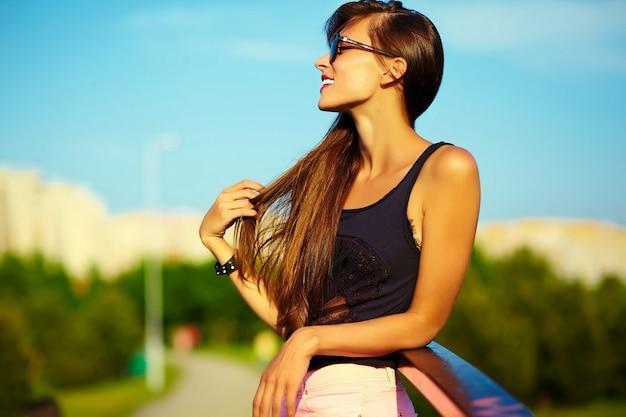 Engraçado elegante sexy sorridente modelo mulher jovem e bonita banhos de sol em pano hippie brilhante de verão no parque