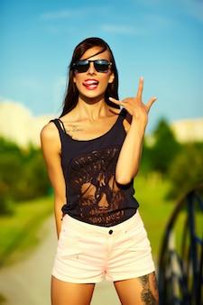 Engraçado elegante sexy sorridente modelo mulher jovem e bonita banhos de sol no pano brilhante hipster de verão no parque