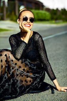 Engraçado elegante sexy sorridente modelo mulher jovem e bonita loira em roupas de verão preto hipster sentado na rua