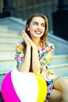 Engraçado elegante sexy sorridente mulher jovem e bonita modelo no verão brilhante hipster pano vestido sentado na rua com bola colorida