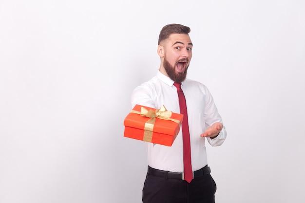 Engraçado empresário apresentar caixa de presente para você. interior, foto de estúdio, isolado em fundo cinza