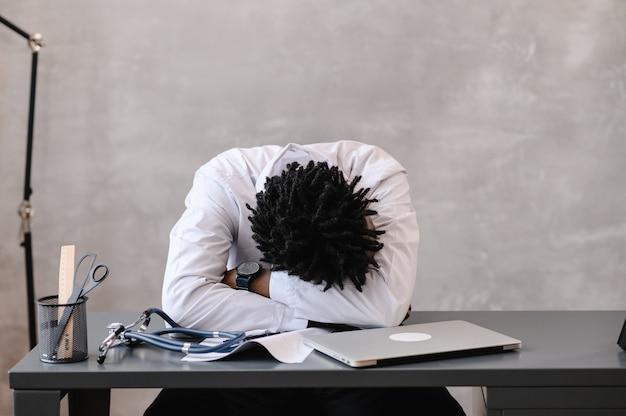 Engraçado entediado no trabalho trabalhador médico afro-americano adormecendo na mesa do escritório