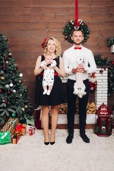 Engraçado família em pé perto da lareira segurando cachorro e filho nas mãos e sorrindo