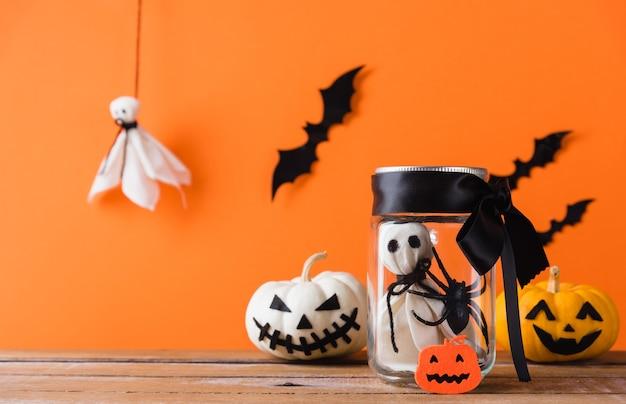 Engraçado fantasma de decoração de halloween com cara assustadora em vidro de frasco e fantasma de abóbora fofo