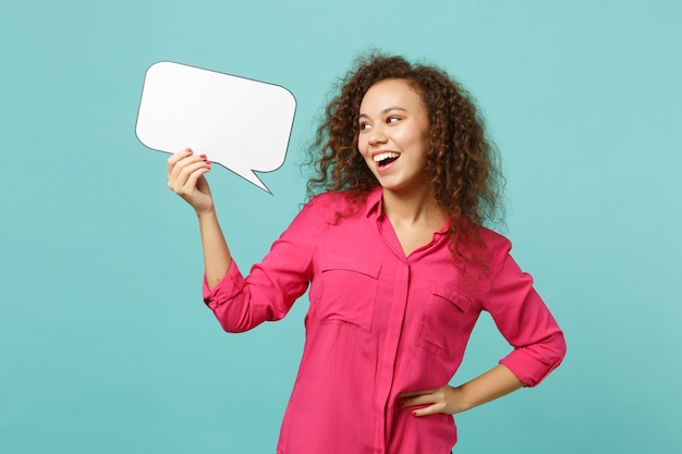 Engraçado garota africana em roupas casuais segurando vazio em branco say nuvem, balão de fala isolado no fundo da parede azul turquesa no estúdio. conceito de estilo de vida de emoções sinceras de pessoas. simule o espaço da cópia.