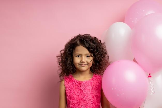 Engraçado garoto atraente com cabelo encaracolado, em pé perto de balões de ar rosa e branco na festa de aniversário, com um lindo vestido, sorrindo, isolado na parede rosada com espaço de cópia. infância feliz, férias.