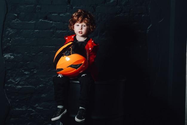 Engraçado garoto encaracolado segurando um capacete nas mãos