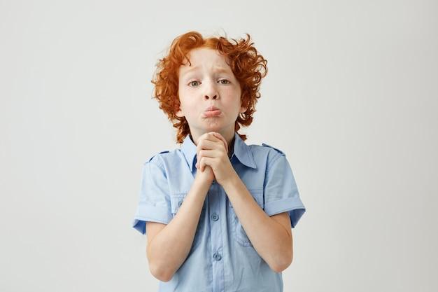 Engraçado garoto ruivo com expressão de rosto triste e culpado tentando se desculpar
