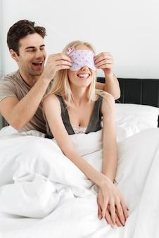 Engraçado homem bonito vestindo sua esposa dormindo máscara