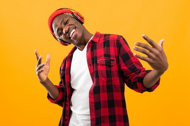 Engraçado homem negro americano elegantemente vestido ouvindo música em fones de ouvido