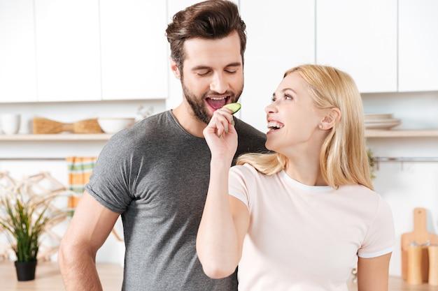 Engraçado jovem casal apaixonado em pé na cozinha e cozinhar