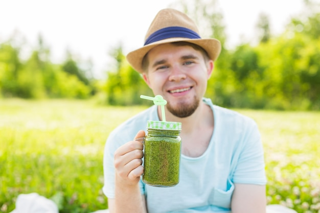 Engraçado jovem contém smoothie de desintoxicação com canudo. conceito de estilo de vida saudável, pessoas e alimentos.