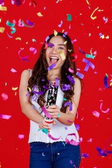 Engraçado jovem e curar menina asiática segurando e soprando poppers de festa com engraçado e feliz. estúdio filmado em fundo vermelho.