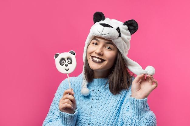 Engraçado jovem em pé com o gostoso panda-pirulito na mão e um chapéu na cabeça em um fundo rosa.