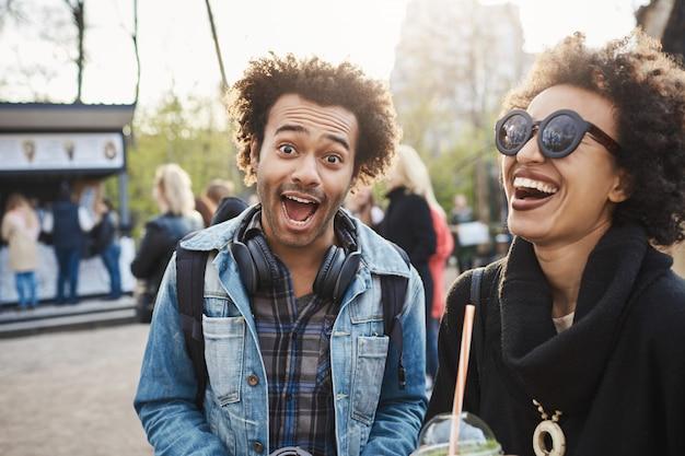 Engraçado jovem emotivo de pele escura com corte de cabelo afro, fazendo careta para a câmera enquanto passa um tempo no parque com o melhor amigo, bebendo chá e curtindo a noite adorável.