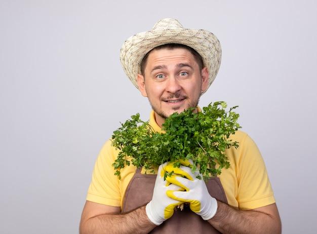 Engraçado jovem jardineiro vestindo macacão e chapéu em luvas de trabalho segurando ervas frescas sorrindo com uma cara feliz