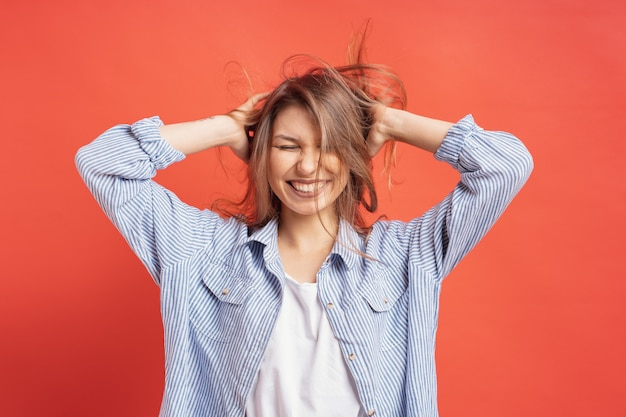 Engraçado, linda garota se divertindo enquanto brincava com o cabelo isolado em uma parede vermelha