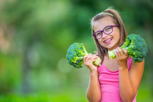 Engraçado linda garota segurando nas mãos repolho roxo e brócolis. fundo desfocado no jardim. jovem pré-adolescente com óculos e aparelho dentário.