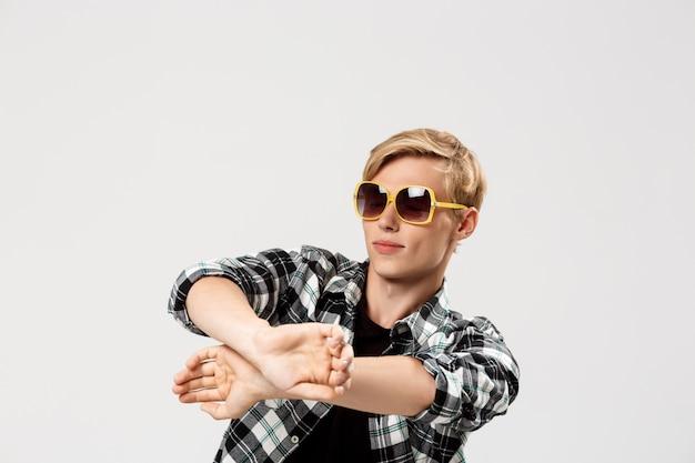 Engraçado loiro jovem bonito usando óculos escuros e camisa xadrez casual dançando na parede cinza
