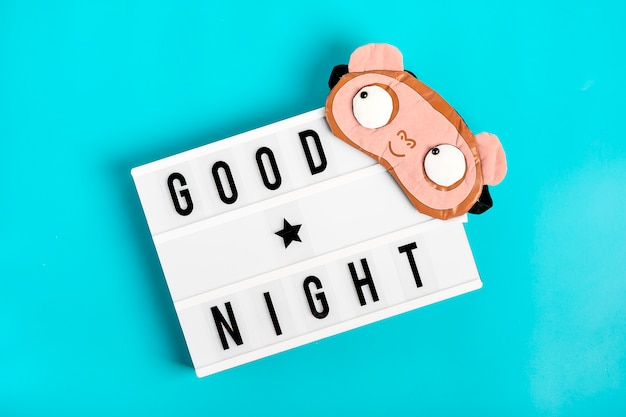 Engraçado, máscara de dormir e lightbox com citação boa noite em fundo azul flat lay