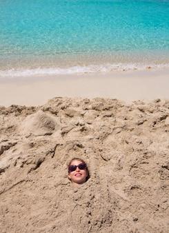 Engraçado, menina, tocando, enterrado, em, areia praia, sorrindo, óculos de sol